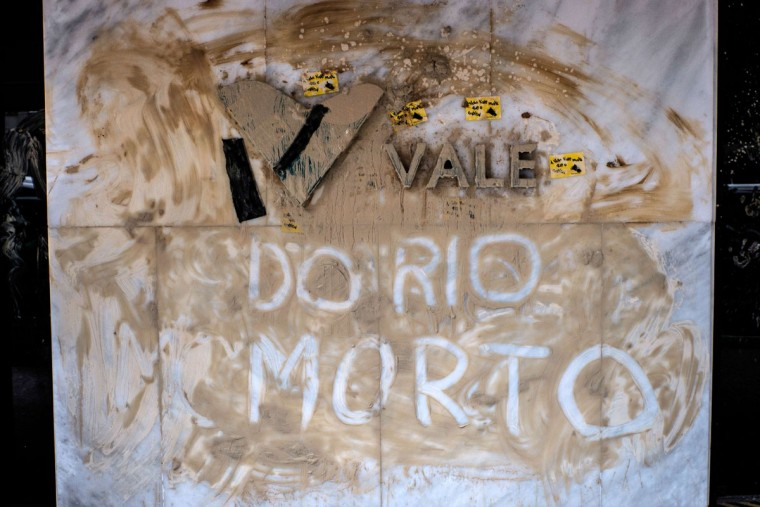 """View of the façade of Brazilian mining company Vale headquarters reading """"Vale of dead Rio"""" after protesters threw muddy water on it in Rio de Janeiro, Brazil, on November 16, 2015. The bursting of two dams at a mine operated by Brazilian company Samarco - equally owned by Vale and Australian BHP Billiton- unleashed torrents of waste that flattened a village in Minas Gerais State on November 5 killing ten people. Brazilian mining firm Samarco promised Monday to pay at least $260 million for damage from the bursting, prosecutors said. (YASUYOSHI CHIBA/AFP/Getty Images)"""