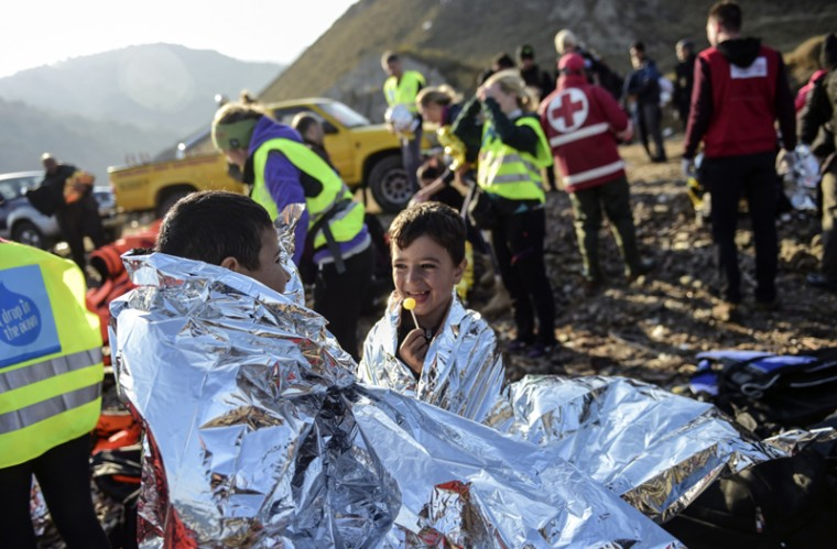 Syrian boys smile and eat candies on the beach, after arriving on the Greek island of Lesbos along with other migrants and refugees, on Tuesday, after crossing the Aegean Sea from Turkey.  At least eight people drowned when a boat carrying migrants from Turkey sank off the Greek island of Kos, the coastguard said. They were the latest of nearly 3,500 deaths at sea this year among people making desperate bids to flee war and poverty and to reach Europe, according to UN figures. European leaders tried to focus on joint action with Africa to tackle the migration crisis, as Slovenia became the latest EU member to act on its own by barricading its border. (BULENT KILIC/AFP/Getty Images)