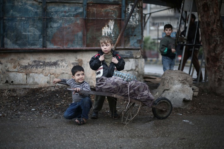 Syrian children take a break from pushing a trolley carrying firewood in the town of Kfar Batna, on the outskirts of the capital Damascus, on November 17, 2015. The annual birth rate in Syria has fallen by more than half since the civil war broke out in 2011, Al-Watan newspaper reported. (AMER ALMOHIBANY/AFP/Getty Images)