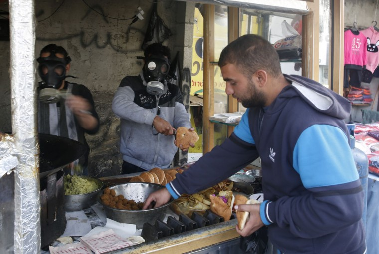 Palestinian Falafel vendors wear gas masks as they prepare food near clashes with Israeli soldiers following a protest in the West Bank city of Hebron, Wednesday, Nov 4, 2015. (AP Photo/Nasser Shiyoukhi)