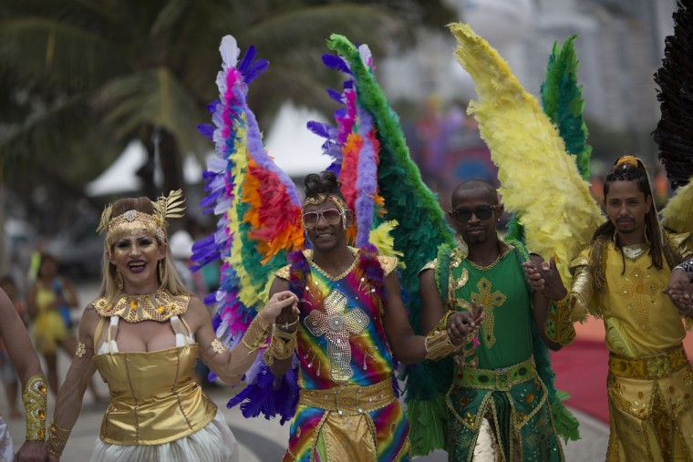 People pose for the picture as they wear feathered angel wings during the Gay Pride Parade at Copacabana beach, in Rio de Janeiro, Brazil, Sunday, Nov. 15, 2015. (AP Photo/Leo Correa)