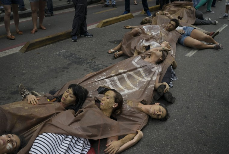 People perform during a protest against the Brazilian mining company Vale, in Rio de Janeiro, Brazil, Monday, Nov. 16, 2015. The demonstrators demand that the company take responsibility for the damage caused by two dams that burst at its iron ore mine, that wiped out a village in the southeastern state of Minas Gerais. (AP Photo/Leo Correa)