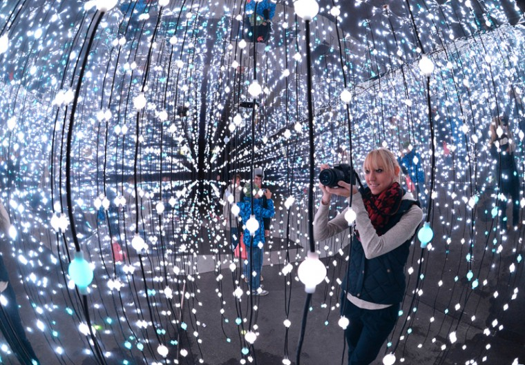 "In this Oct. 8 photo, a woman takes a photograph in the light installation ""Light Walk"" during the light and science festival in Jena, eastern Germany. (Martin Schutt/dpa via AP)"