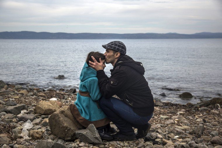 A Syrian man kisses his daughter shortly after disembarking from a dinghy at a beach on the Greek island of Lesbos after crossing the Aegean sea from the Turkish coast on Monday. (Santi Palacios/AP)