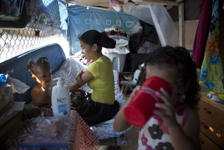 Kifency Kinny, center, applies lotion to her arm and her 1-year-old son, J. Jee Suzuki while Kinny's niece, Keioleen Helly, drinks water in their makeshift tent at a homeless encampment in the Kakaako district of Honolulu. Homelessness in Hawaii has grown in recent years, leaving the state with 487 homeless per 100,000 people, the nation's highest rate per capita, ahead of New York and Nevada, according to federal statistics. (AP Photo/Jae C. Hong)