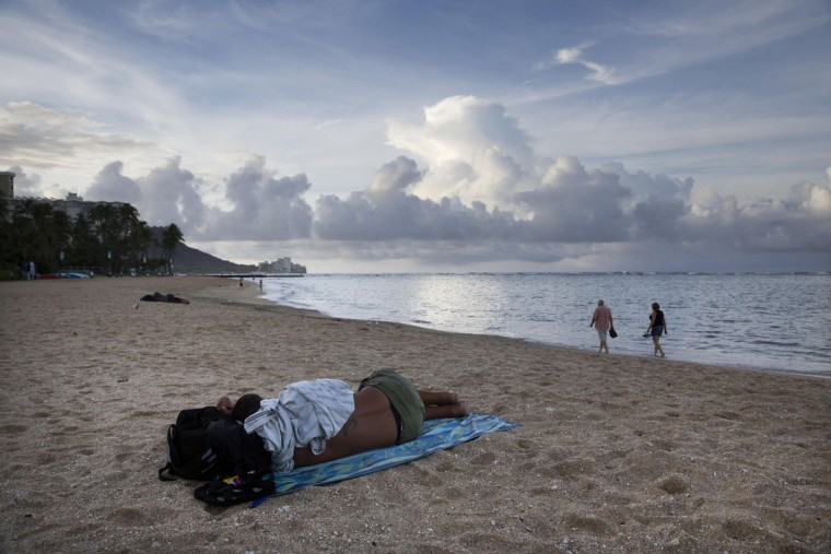 A homeless man sleeps on Fort DeRussy in Waikiki as two tourists take a morning stroll along the beach in Honolulu. In 2014, after visitors complained about too many homeless people living near Waikiki Beach, the city banned sitting and lying down on sidewalks. (AP Photo/Jae C. Hong)