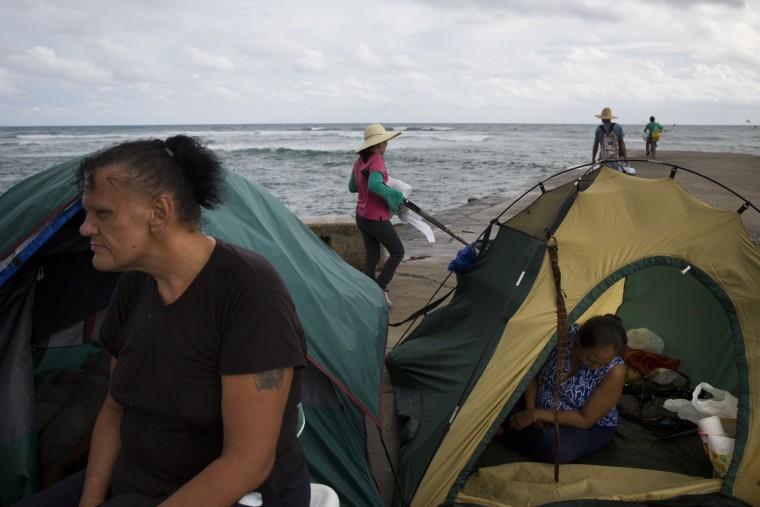 Two homeless people rest with their tents pitched on a sidewalk as a group of anglers arrive to fish at Kewalo Basin Harbor in Honolulu. Homelessness in Hawaii has grown steadily in recent years, leaving the state with the nation's highest rate of homeless people per capita. (AP Photo/Jae C. Hong)