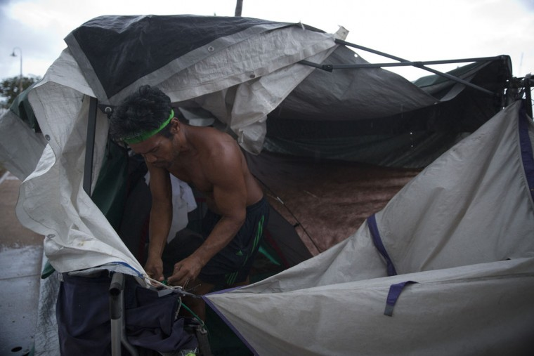 A homeless man fixes his tent to prepare for an approaching storm in the Kakaako district of Honolulu. Homelessness in Hawaii has grown steadily in recent years, leaving the state with the nation's highest rate of homeless people per capita. (AP Photo/Jae C. Hong)