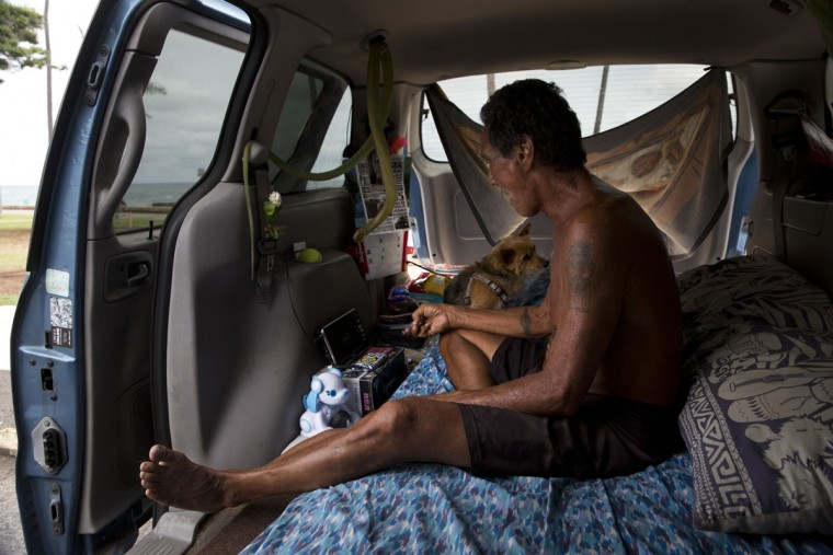 Dexter Lii, a retired surf instructor, and his dog sit in a minivan in Kakaako Waterfront Park in Honolulu. The number of homeless people in Hawaii grew over the past five years, and the state's population of unsheltered families ballooned 46 percent from 2014 to 2015, said Scott Morishige, state coordinator on homelessness. (AP Photo/Jae C. Hong)