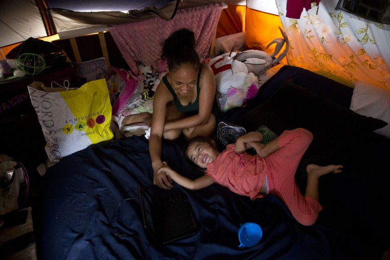 Tabatha Martin, 27, plays with her 4-year-old daughter, Thalia, in their tent at a homeless encampment in the Kakaako district of Honolulu. The Martins became homeless when Tracy, the father, had a heart attack after working long hours as a kitchen manager, they said. After exhausting their savings, they couldn't afford rent for their Pearl City apartment and wound up on the street. (AP Photo/Jae C. Hong)