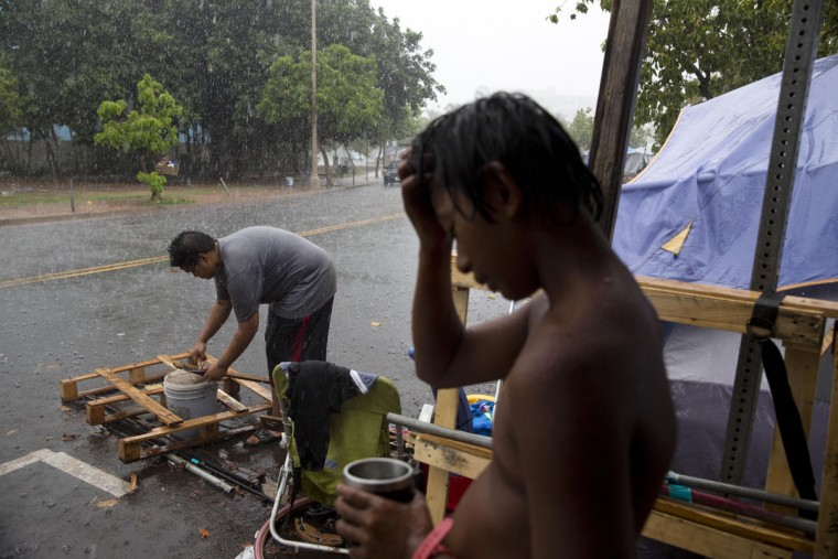 "A boy who goes by ""M.J.,"" is soaked in rain as a woman pulls nails from a pallet to use them to build a makeshift tent at a homeless encampment in the Kakaako district of Honolulu. The camp, one of the nation's largest homeless encampment and once home to hundreds of people, recently cleared by Hawaii officials. Homelessness in Hawaii has grown in recent years, leaving the state with 487 homeless per 100,000 people, the nation's highest rate per capita, ahead of New York and Nevada, according to federal statistics. (AP Photo/Jae C. Hong)"