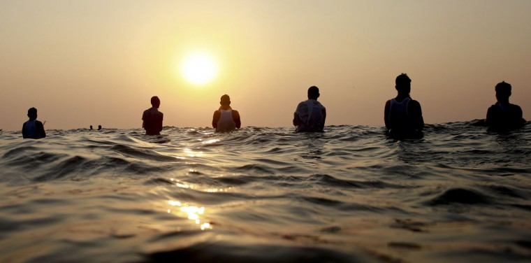 Hindu devotees offer prayers standing in the waters of the Arabian Sea at sun set during Chhath Puja festival in Mumbai, India, Tuesday, Nov 17, 2015. On Chhath, an ancient Hindu festival, rituals are performed to thank the Sun god for sustaining life on earth. (AP Photo/Rafiq Maqbool)