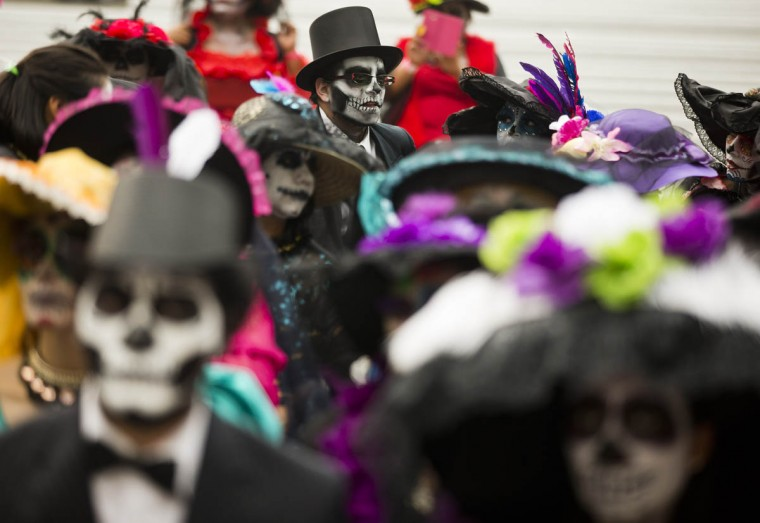 "People dressed as ""Catrinas"" commemorate Day of the Dead, a holiday that honors the deceased, during a Catrina Fest in Mexico City, Saturday, Oct. 31 2015. The figure of a skeleton wearing an elegant broad-brimmed hat was first done as a satirical engraving by artist Jose Guadalupe Posada sometime between 1910 and his death in 1913. (Esteban Felix/AP photo)"