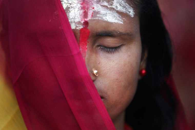 A Nepalese woman offers prayers on the banks of the Bagmati River during the Chhath Puja festival in Kathmandu, Nepal. On Chhath, an ancient Hindu festival, rituals are performed to thank the Sun god for sustaining life on earth. (AP Photo/Niranjan Shrestha)