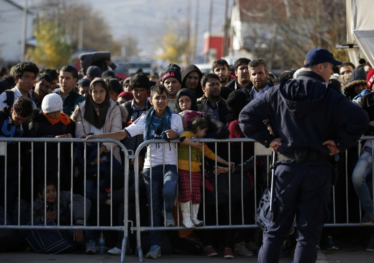 Migrants wait to register with the police at the refugee center in the southern Serbian town of Presevo on Monday.  Refugees fleeing war by the tens of thousands fear the Paris attacks could prompt Europe to close its doors, especially after police said a Syrian passport found next to one attacker's body suggested its owner passed through Greece into the European Union and on through Macedonia and Serbia last month. (Darko Vojinovic/AP)