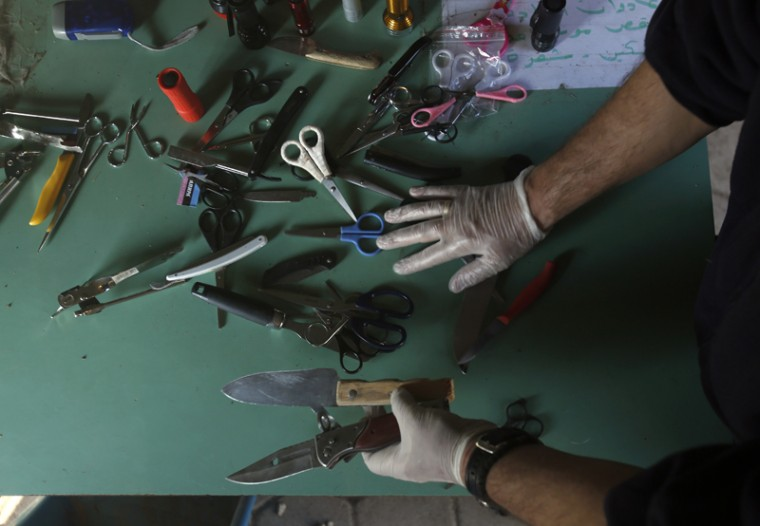 A Serbian police officer shows confiscated items such as scissors and knives, at a refugee center in the southern Serbian town of Presevo, on Monday. Refugees fleeing war by the tens of thousands fear the Paris attacks could prompt Europe to close its doors, especially after police said a Syrian passport found next to one attacker''s body suggested its owner passed through Greece into the European Union and on through Macedonia and Serbia last month. (Darko Vojinovic/AP)