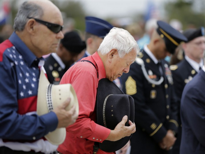 Army veterans Don Doyle, left, and Salvado Campos Jr., right, hold cowboy hats during an invocation as they attend a Veteran's Day observance at Fort Sam Houston National Cemetery, Wednesday, Nov. 11, 2015, in San Antonio. (AP Photo/Eric Gay)