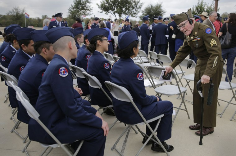 Army veteran James F. Gerald, 85, right, visits with members of the South Side High School Junior ROTC following a Veteran's Day observance at Fort Sam Houston National Cemetery, Wednesday, Nov. 11, 2015, in San Antonio. (AP Photo/Eric Gay)