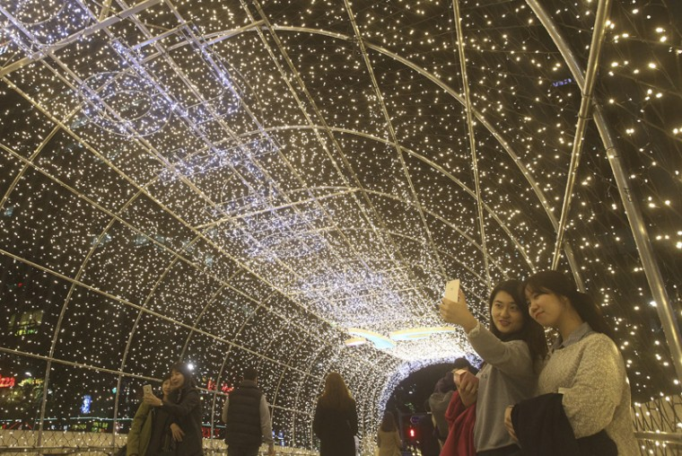 In this file photo, visitors take pictures under a tunnel of lights on the eve of Seoul Lantern Festival, which will be held through Nov. 22, along Cheonggye stream in Seoul, South Korea. (Ahn Young-joon/AP)