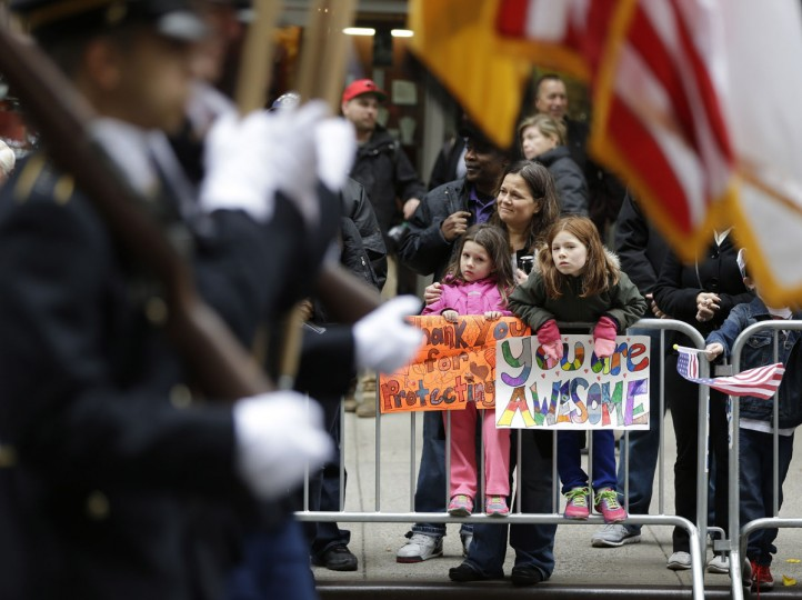 Sophie, 8, right, and her sister, Ruby O'Hara hold signs as they watch the annual Veteran's Day parade with their mother, Mary Ann O'Hara, in New York, Wednesday, Nov. 11, 2015. (AP Photo/Seth Wenig)