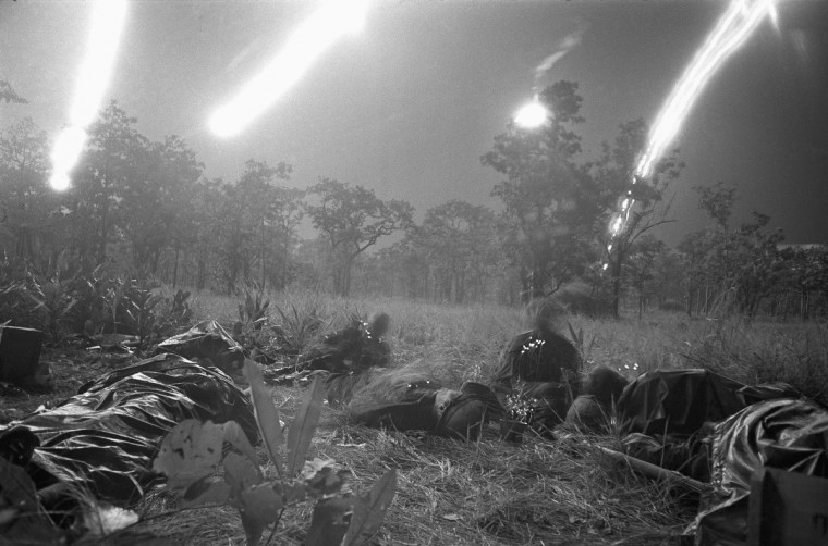 Flares from planes light a  field covered with dead and wounded of ambushed battalion of the U.S. 1st Cavalry Division in the Ia Drang Valley, Vietnam, November 18, 1965. During fierce battle that has been raging since Nov.14, 1965. Units of the division have been battling to hold its lines against what is estimated to be a regiment of North Vietnamese soldiers.  Bodies of the slain soldiers were carried to this clearing with their gear to await evacuation by helicopter.  (Rick Merron/AP Photo)