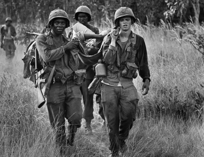 U.S. cavalrymen carry a fellow soldier to an evacuation zone after he was seriously wounded in a North Vietnamese ambush in South Vietnam's Ia Drang Valley, mid November 1965. (Peter Arnett/AP Photo)