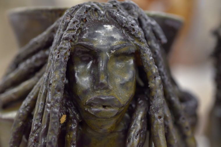 The head on this vase was an experiment for Murjoni Merriweather to see how the dreadlocks fell onto the shape of the vase. The green glaze was a surprise after the vase was fired twice.  (Algerina Perna/Baltimore Sun)