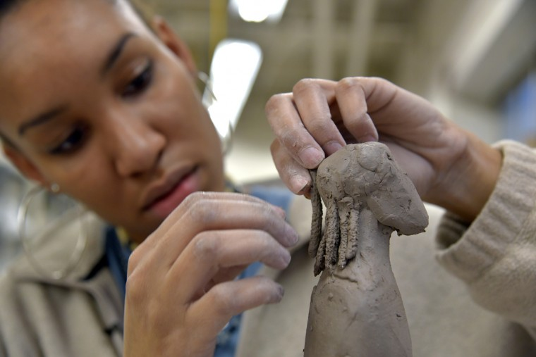 Art student Murjoni Merriweather places dreadlocks on a male figure's head. Murjoni Merriweather works on her art at the MICA ceramics studio. (Algerina Perna/Baltimore Sun)