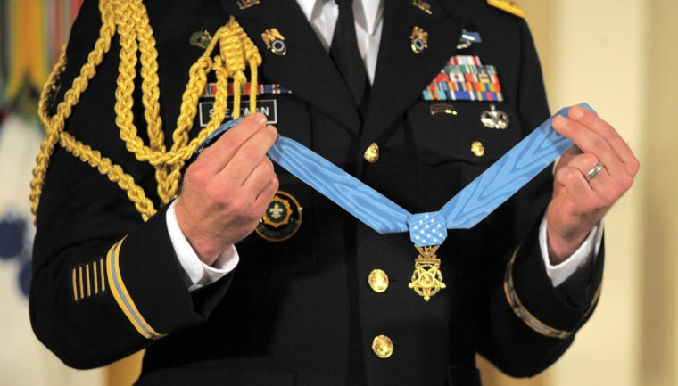 A member of the military holds the Medal of Honor before it's presented. In the White House East Room, President Barack Obama presents Captain Florent A. Groberg, U.S. Army (Ret), the Medal of Honor for conspicuous gallantry for his courageous actions while serving as a Personal Security Detachment Commander for Task Force Mountain Warrior, 4th Infantry Brigade Combat Team, 4th Infantry Division during combat operations in Asadabad, Kunar Province, Afghanistan on August 8, 2012. He is the tenth living recipient to be awarded the Medal of Honor for actions in Afghanistan. (Algerina Perna, Baltimore Sun)