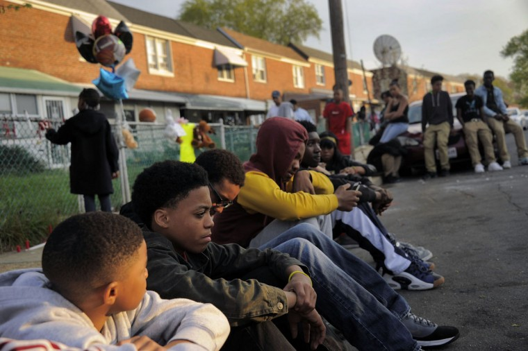From left foreground, Maurice Barksdale, 9 Dante Wooding, 15, Ahmad Hunter, 16, and William Winder, 18 (red hood) sit with others during an impromptu candlelight vigil at 615 Roundview Road for the third murder victim in three days in Cherry Hill on April 22, 2014. (Karl Merton Ferron/Baltimore Sun Staff)