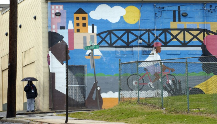 A mural in Cherry Hill provides little shelter for a woman waiting for a ride on Nov. 9, 2007. (Baltimore Sun photo by Jed Kirschbaum)