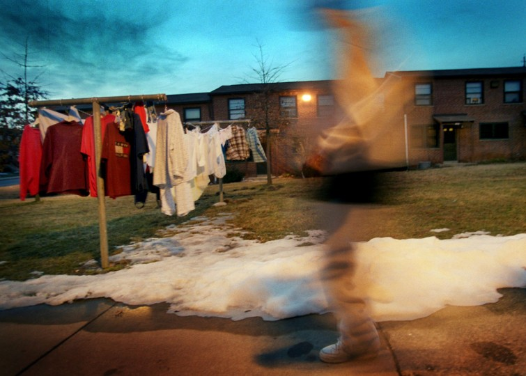 A person blurs as he walks through the courtyard of public housing in the Cherry Hill neighborhood near the 3400 block of Round Road on March 8, 2003. (GLENN FAWCETT/SUN STAFF)