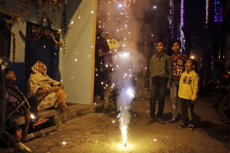 Indians watch a firecracker light up during Diwali celebrations in New Delhi, India, Wednesday, Nov. 11, 2015. Diwali, the festival of lights, is one of Hinduism's most important festivals dedicated to the worship of Lakshmi, the Hindu goddess of wealth. (AP Photo/Altaf Qadri)