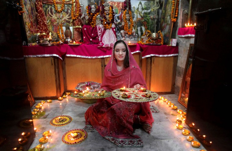 A Pakistani Hindu woman lights candles during Diwali celebrations at a local temple in Lahore, Pakistan, Wednesday, Nov. 11, 2015. (AP Photo/K.M. Chaudary)