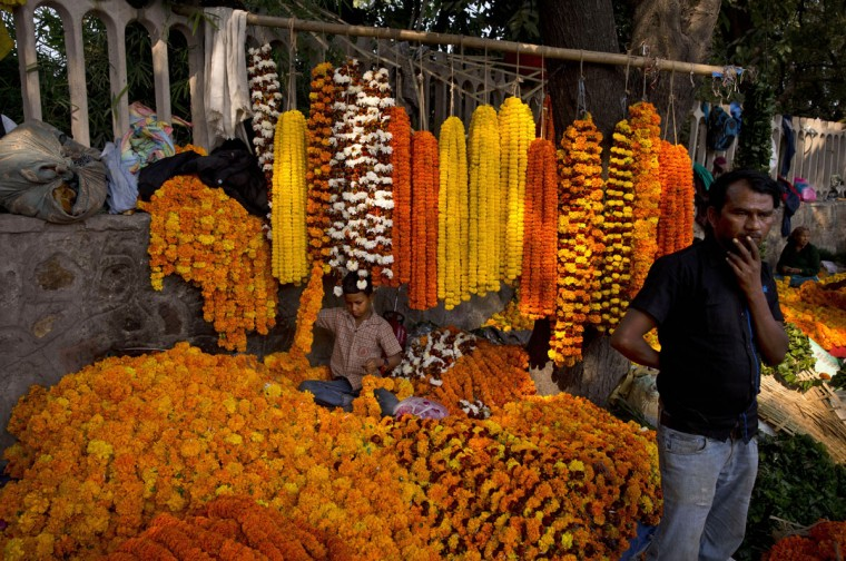 A boy prepares garlands of marigold at a makeshift flower market as people drop by to purchase flowers and decorate their homes on the occasion of Diwali festival, in New Delhi, India, Wednesday, Nov. 11, 2015. (AP Photo/Saurabh Das)