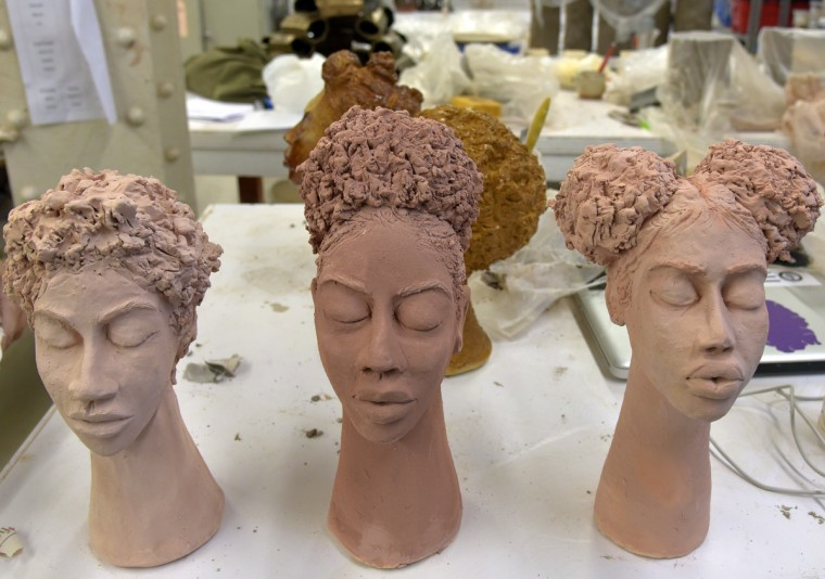 Three unfired heads. They were the same concepts of natural hair based on friends and people that she sees on daily routine. They have glaze but haven't been fired. Merriweather wanted to experiment with elongated necks.  (Algerina Perna/Baltimore Sun)