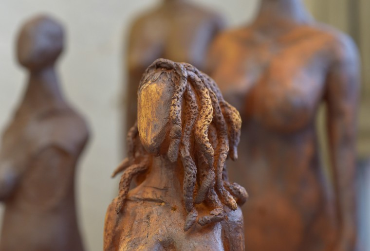 A red iron oxide wash creates earth tones suggesting the skin tones of African Americans. The hairstyle on this female figure is taken from a woman she saw on the train who had dreadlocks flipped to the side.  (Algerina Perna/Baltimore Sun)