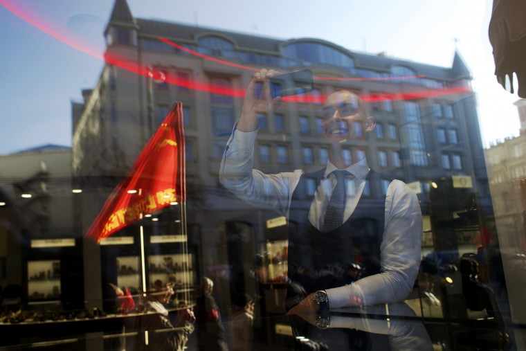 A man from behind a window, take photos with a phone of the Communist demonstration held to mark the 98th anniversary of the Bolshevik revolution in Moscow, Russia, Saturday, Nov. 7, 2015. For decades Nov. 7 used to be a holiday celebrating the 1917 Bolshevik Revolution and which is no longer a public holiday in Russia. (AP Photo/Ivan Sekretarev)