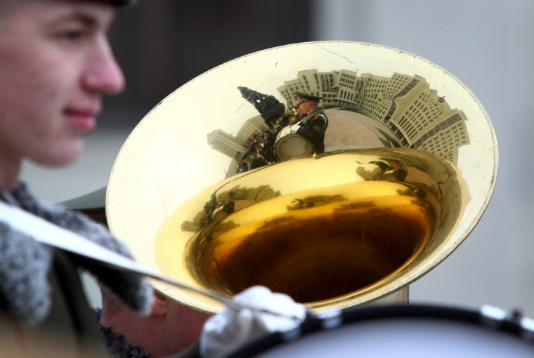 The monument to Vladimir Lenin, Soviet founder, and a building of the Belarusian parliament are reflected in the trumpet of military musician during the celebration of the anniversary of the 1917 Bolshevik revolution in Minsk, Belarus, Saturday, Nov. 7, 2015. This is the state holiday in Belarus. (AP Photo/Sergei Grits)