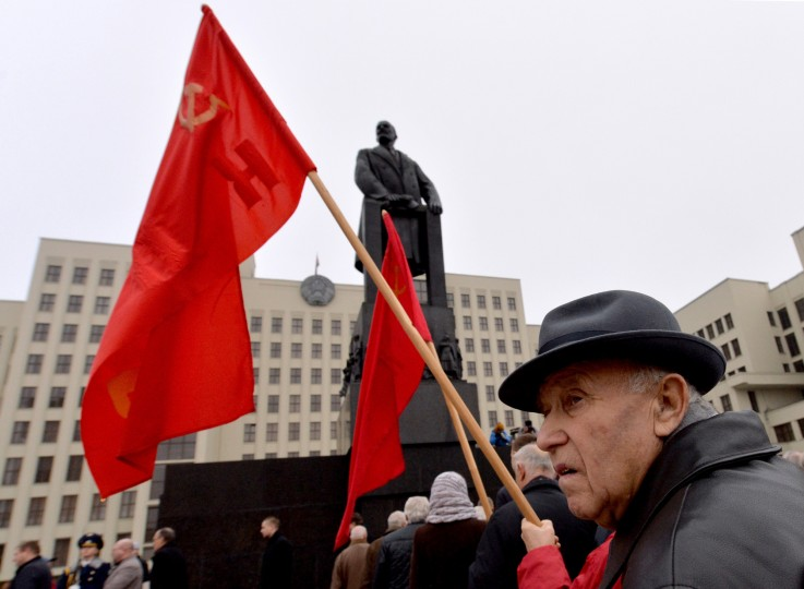 A man holds a red flag in front of a monument to the Soviet Union founder Vladimir Lenin during a rally to mark the 98th anniversary of Russia's Bolshevik Revolution in central Minsk on November 7, 2015. (Maxim Malinovsky/AFP-Getty Images)