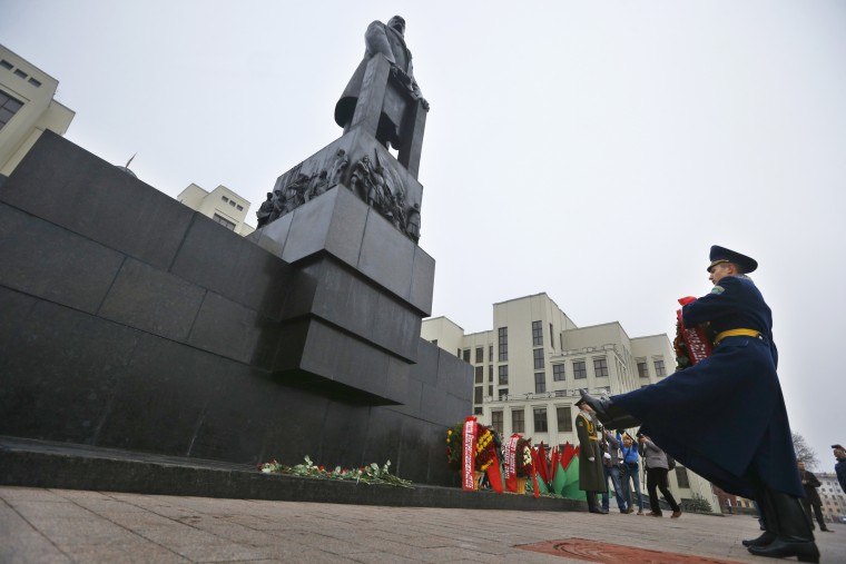 Belarusian honor guard soldiers carry flowers to the monument to Soviet founder Vladimir Lenin during the celebration of the anniversary of the 1917 Bolshevik revolution in Minsk, Belarus, Saturday, Nov. 7, 2015. This is the state holiday in Belarus. A building of the Belarusian parliament is in the background. (AP Photo/Sergei Grits)