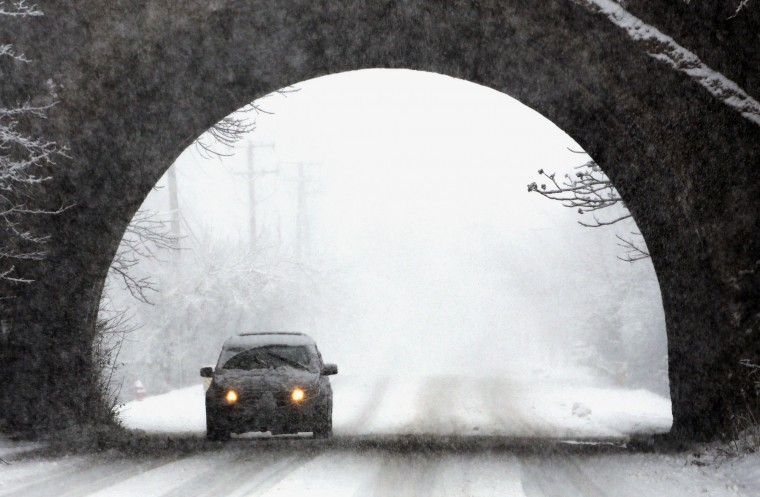 A car moves slowly on the road during a snowstorm, Saturday, Nov. 21, 2015, in Northbrook, Ill. The first significant snowstorm of the season blanketed some parts of the Midwest with more than a foot of snow and more was on the way Saturday, creating hazardous travel conditions and flight delays. (AP Photo/Nam Y. Huh)