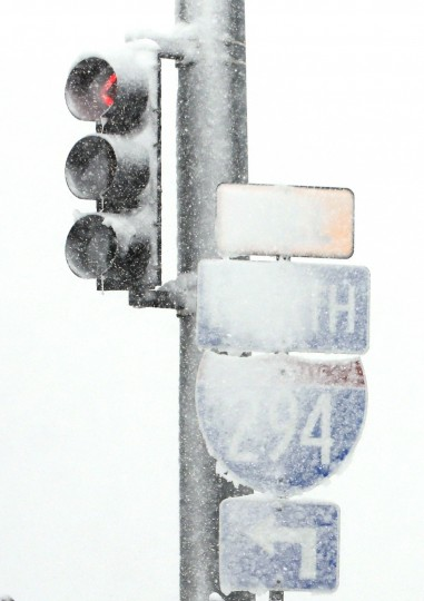 A traffic signal and signs are covered by snow on the road on Saturday, Nov. 21, 2015, in Wheeling, Ill. The first significant snowstorm of the season blanketed some parts of the Midwest with more than a foot of snow and more was on the way Saturday, creating hazardous travel conditions and flight delays. (AP Photo/Nam Y. Huh)