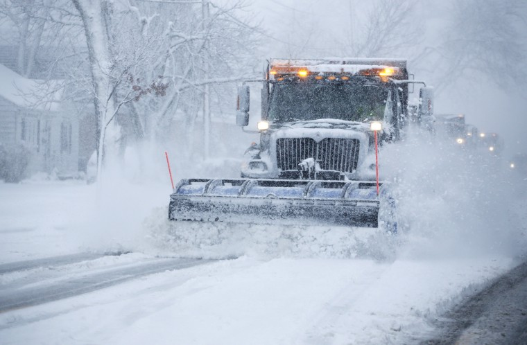 Snow is plowed from the street during a heavy snowy day on Saturday, Nov. 21, 2015, in Northbrook, Ill. The first significant snowstorm of the season blanketed some parts of the Midwest with more than a foot of snow and more was on the way Saturday, creating hazardous travel conditions and flight delays. (AP Photo/Nam Y. Huh)