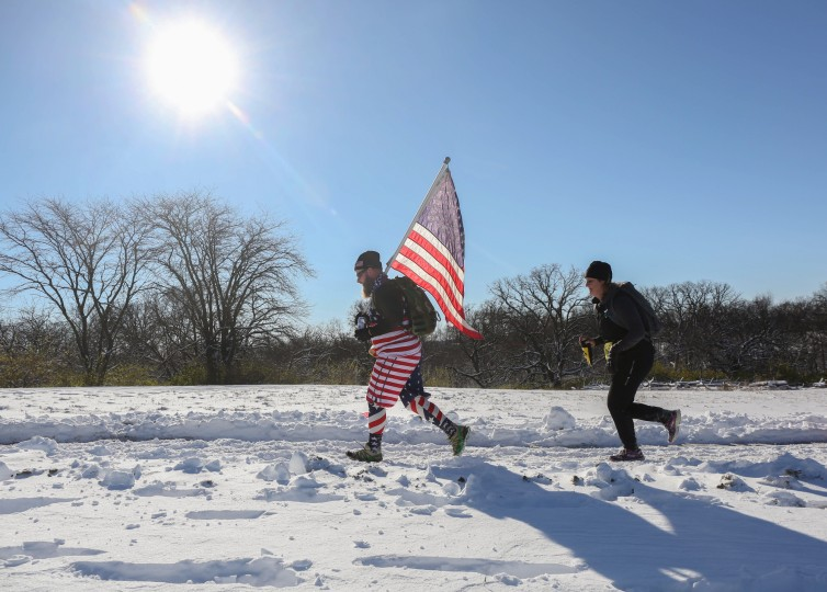 Runners make their way around the rugged course during the Living History Farms run on Saturday, Nov. 21, 2015, in Urbandale, Iowa. Residents are digging out from under more than a foot of snow in some places, while roads over all but the southwest portion of the state remain impassable or partially blocked. (Bryon Houlgrave/The Des Moines Register via AP)