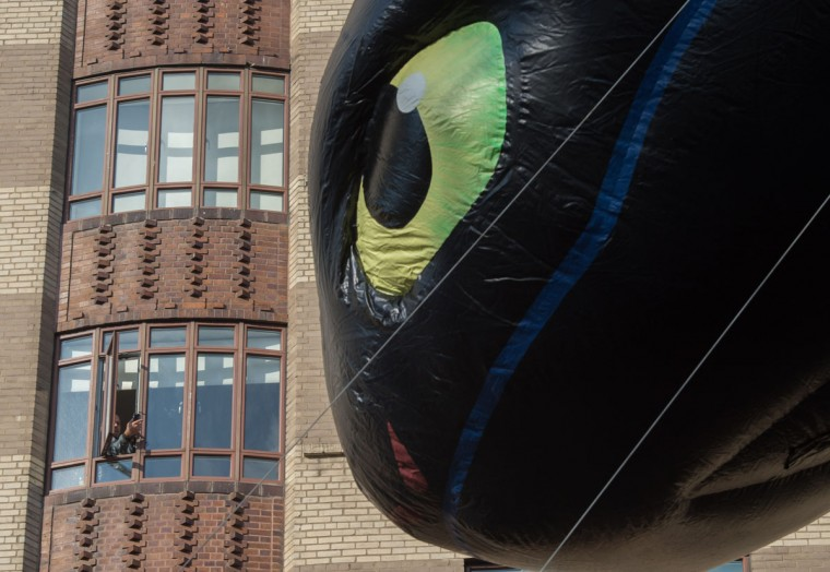 A spectator takes a photo of the balloon Toothless during the Macy's Thanksgiving Day Parade, Thursday, Nov. 26, 2015, in New York. (AP Photo/Bryan R. Smith)