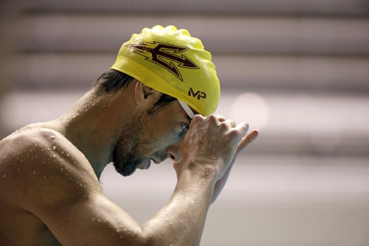 Michael Phelps prepares to enter the water during a practice session for the U.S. Winter Nationals swimming event Wednesday, Dec. 2, 2015, in Federal Way, Wash. (AP Photo/Elaine Thompson)