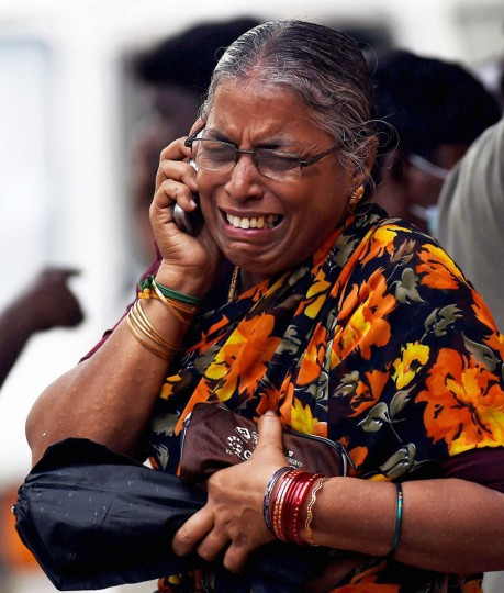In this photo provided by the Press Trust of India, a woman who lost a relative in the floods cries as she speaks on the phone at a hospital in Chennai, India, Friday, Dec. 4, 2015. The relentless rains that lashed the state for three days eased Friday, but the misery of tens of thousands of people was far from over, with large parts of the main city still underwater along with the region's biggest airport. (R. Senthil Kumar/Press Trust of India via AP)