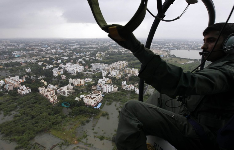 A coastguard sailor surveys an area inundated by floodwaters in Chennai, India, Saturday, Dec. 5, 2015. Although floodwaters have begun to recede, vast swaths of Chennai and neighboring districts were still under 2 1/2 to 3 meters (8 to 10 feet) of water, with tens of thousands of people in state-run relief camps. (AP Photo/Arun Sankar K)