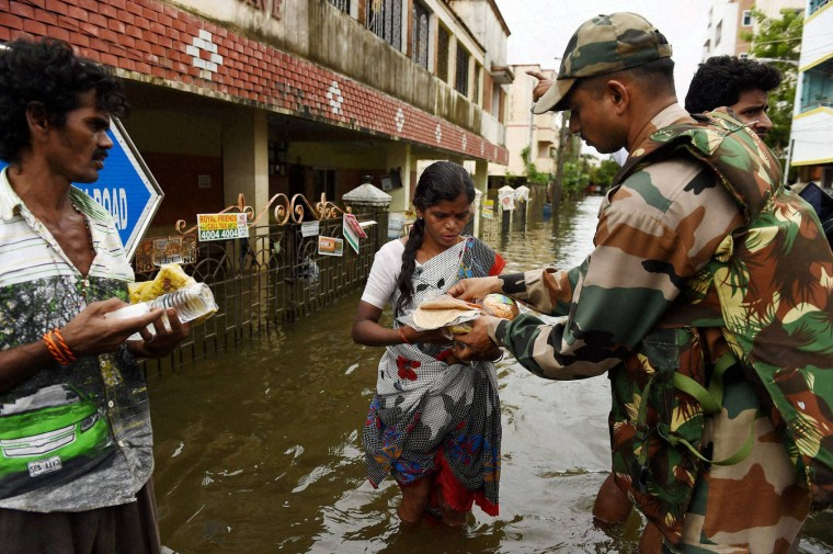 An Indian army soldier distributes relief material to flood affected people in Chennai, India, Saturday, Dec. 5, 2015. Although floodwaters have begun to recede, vast swaths of Chennai and neighboring districts were still under 2 1/2 to 3 meters (8 to 10 feet) of water, with tens of thousands of people in state-run relief camps. (R. Senthil Kumar/Press Trust of India via AP)